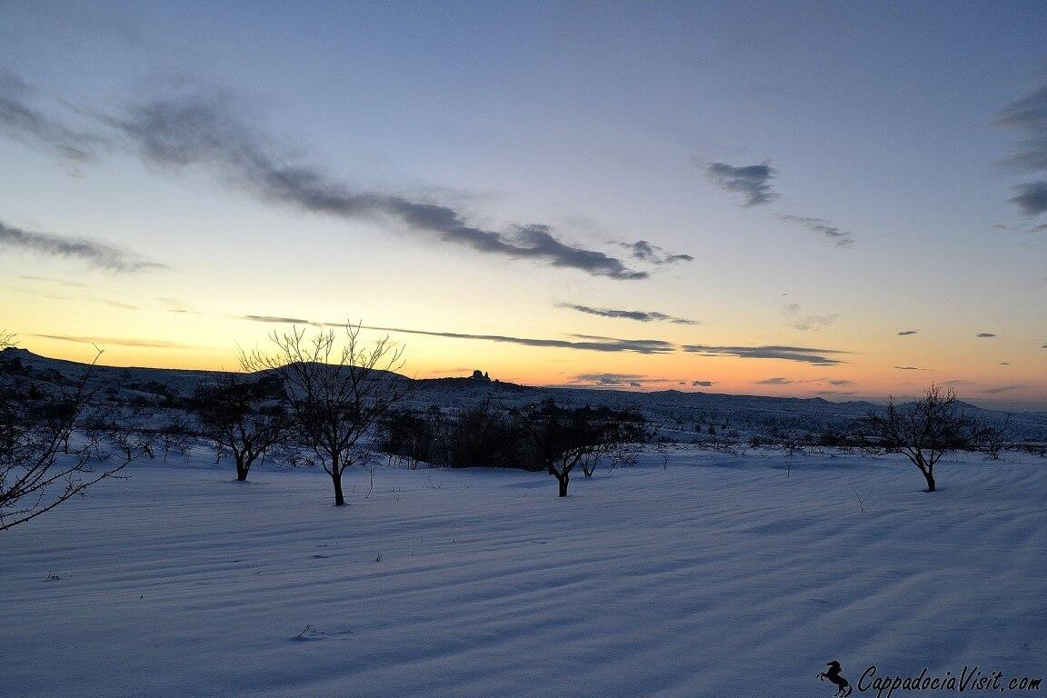 Поля покрытые снегом и закат в Каппадокии