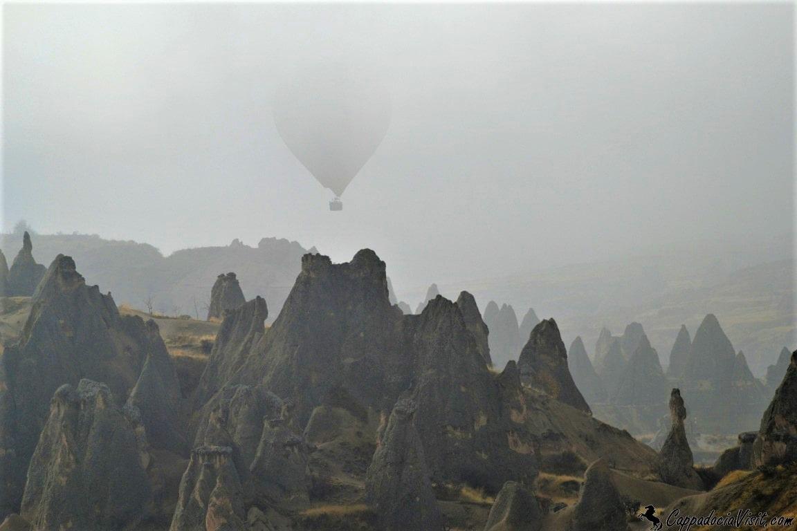 Воздушный шар летит в осеннем тумане над скалами Каппадокии